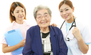 nurses and elderly woman smiling
