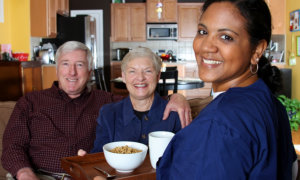 caregiver and elderly couple smiling