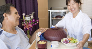 caregiver preparing meal for her patient in bed